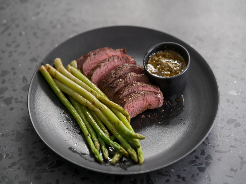 New york steak with asparagus on black plate with pesto sauce