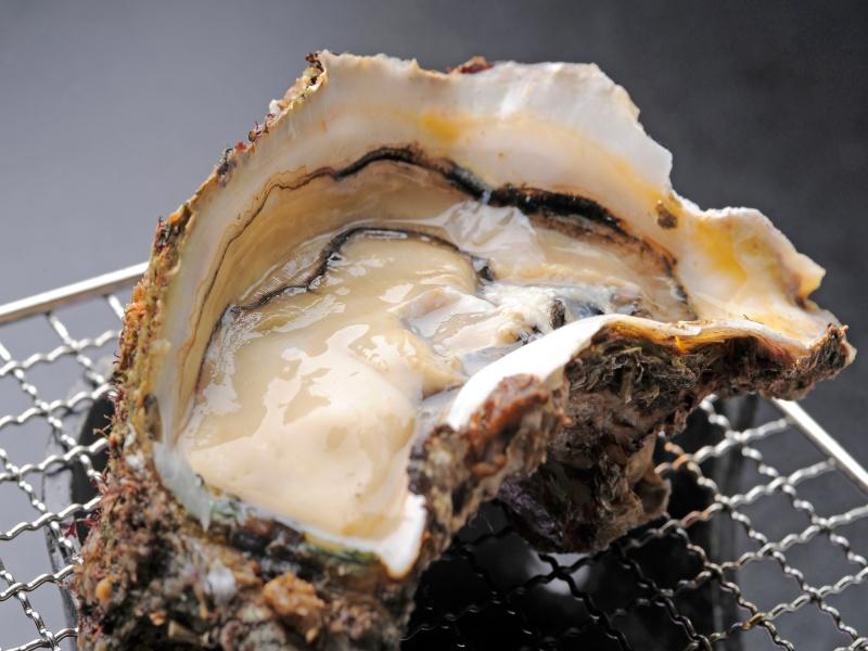 焼き網の上の生カキ 海鮮料理