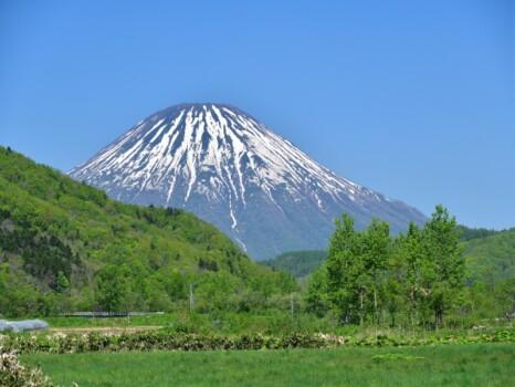 初夏の北海道喜茂別町で里山と残雪の羊蹄山の風景を撮影