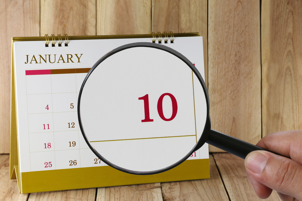 Magnifying glass in hand on calendar you can look tenth day of month,Focus number ten in January,Concept in business and meetings.