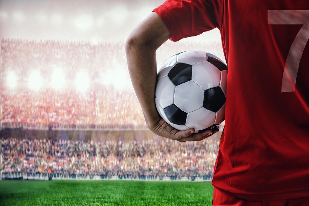 球場でサッカーボールを持つレッドチームのコンセプトのサッカー選手