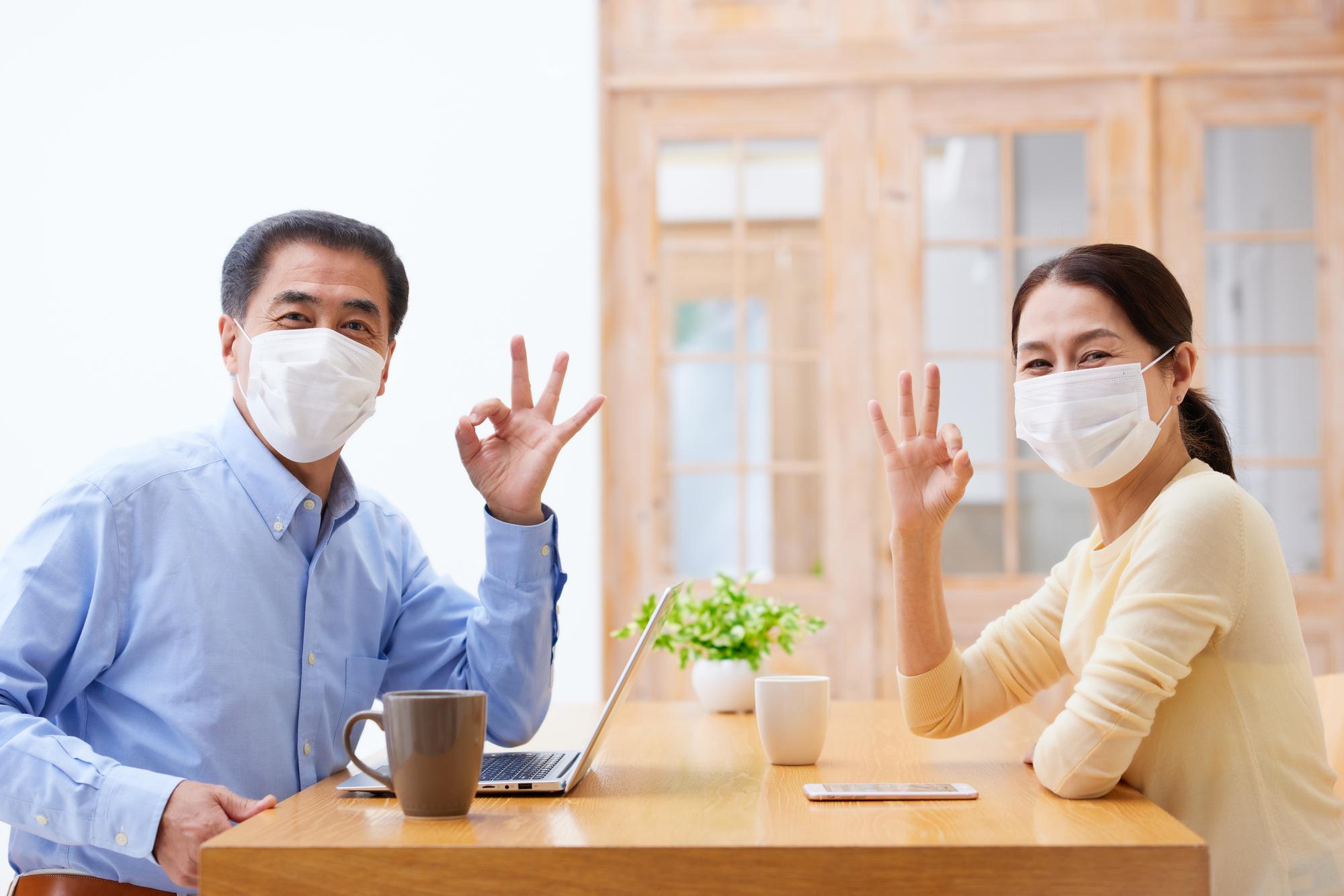 リビングでマスクを付けて話すシニアの夫婦