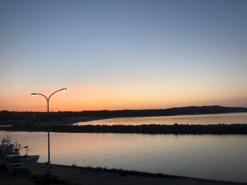 夕焼けに染まる網走川とオホーツク海