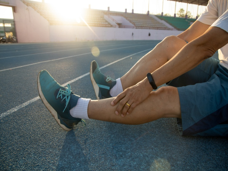 人間は、現場でジョギングをしている間に足に痛みがある。 彼は痛みを感じてマッサージをしている。