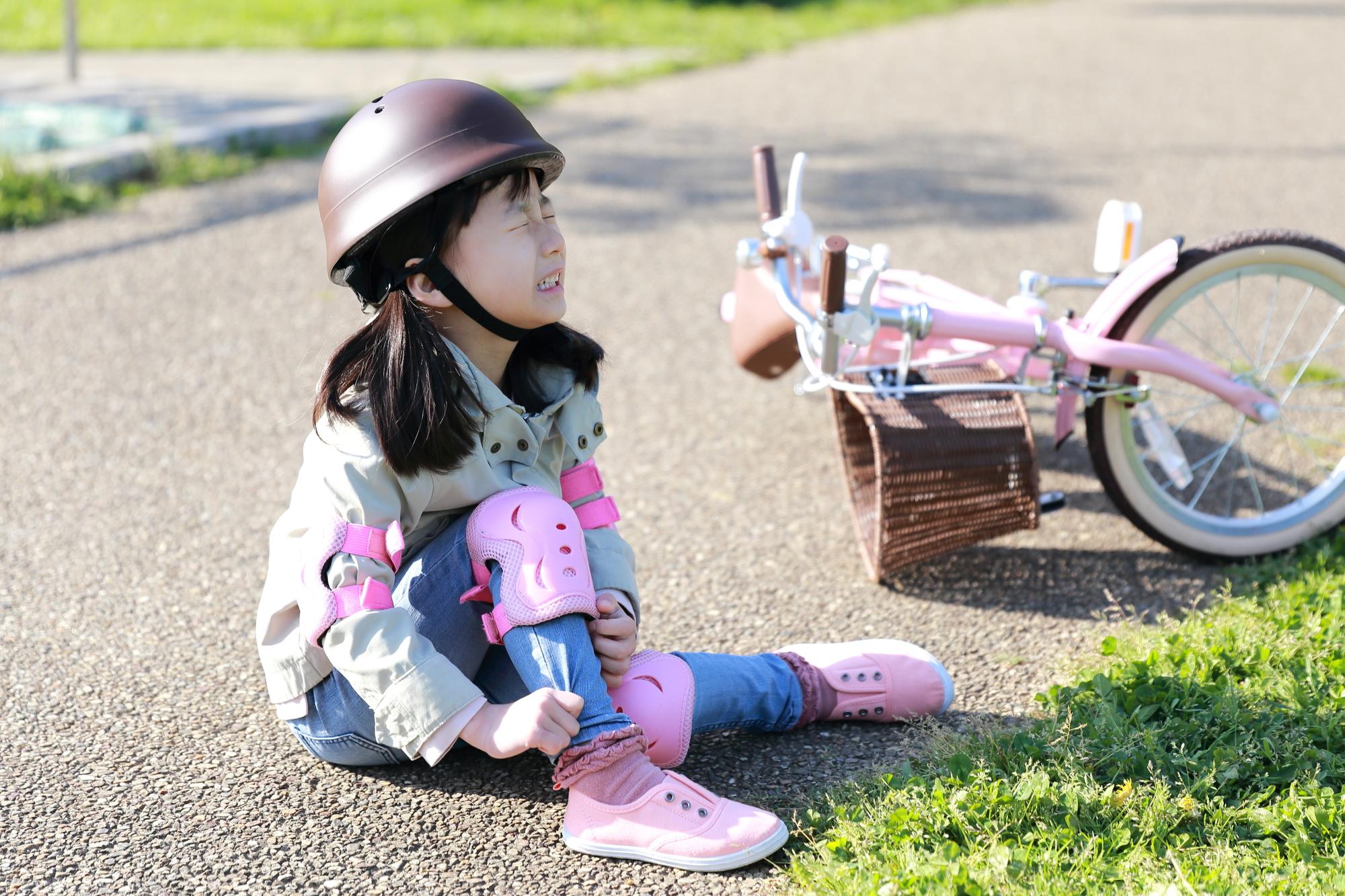 自転車の練習中に転んで怪我をする女の子