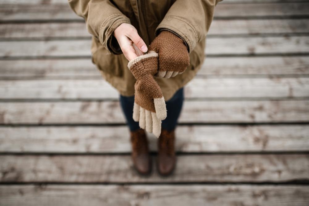 girl puts on her hands warm winter wool gloves